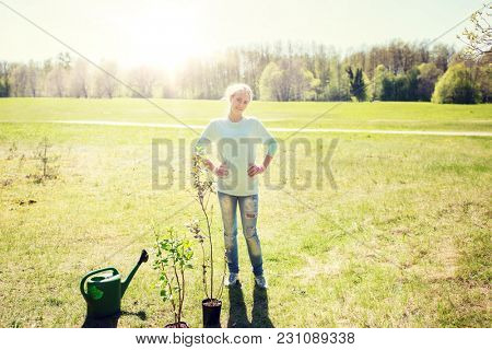 people, volunteering and environment concept - happy young volunteer woman outdoors