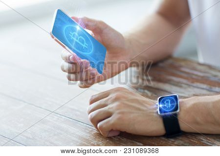 business, technology and cryptocurrency concept - close up of male hand holding smartphone and wearing smart watch with bitcoin on screen