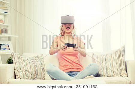 3d technology, virtual reality, gaming, entertainment and people concept - happy young woman with virtual reality headset or 3d glasses playing video game with controller gamepad at home