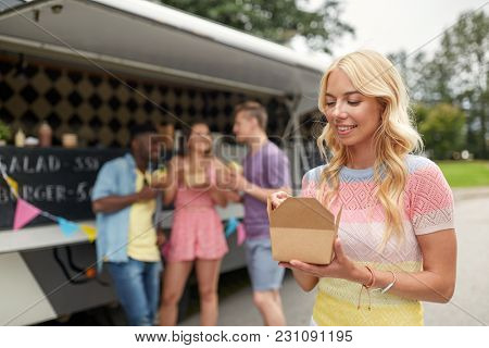 leisure, eating and people concept - happy young woman with wok and friends at food truck