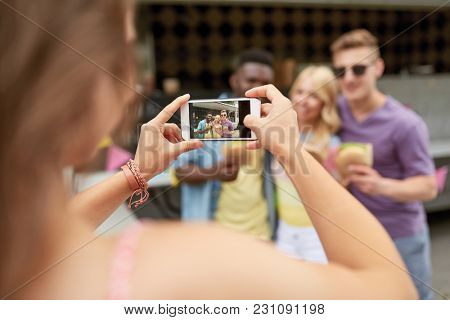 leisure, technology and people concept - young woman taking picture of her happy friends eating hamburgers and wok at food truck
