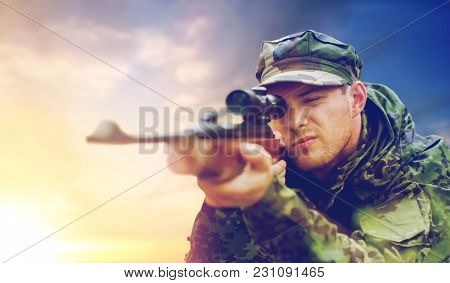 hunting, army, military service and people concept - young soldier, sniper or hunter with gun aiming or shooting over sky background