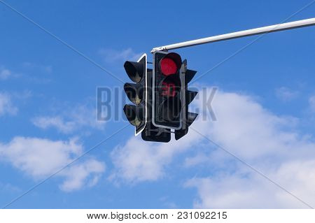 Red Traffic Signal Against A Blue Sky And Clouds. Suspended Device With Digital Display