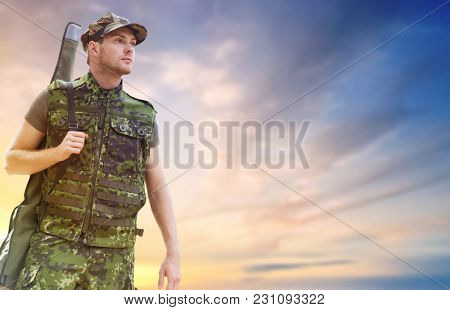 hunting, army, military service and people concept - young soldier, ranger or hunter with gun over sky background