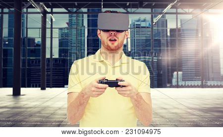 3d technology, virtual reality, entertainment and people concept - happy young man with virtual reality headset playing with game controller gamepad over industrial room and city panorama background
