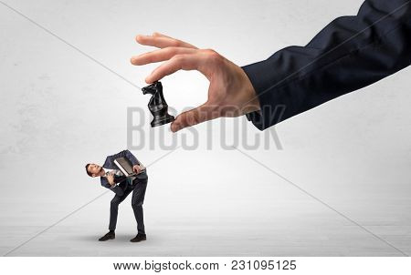 Big hand holding chessman and down little afraid businessman concept in a light space