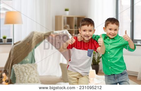 childhood, fashion, friendship and people concept - happy smiling little boys showing thumbs up over kids room and tepee background