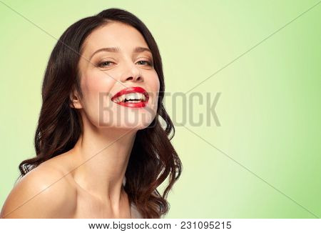 beauty, make up and people concept - happy smiling young woman with red lipstick over green background