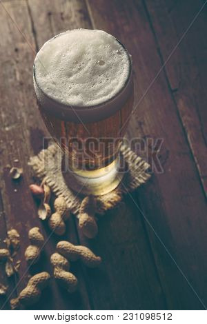 Glass Of Cold Pale Beer Placed On A Burlap Coaster And Some Peanuts On A Rustic Wooden Table. Select