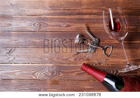 Photo Of Bottle Of Wine, Corkscrew, Wine Glass On Brown, Wooden Background. Empty Place For Text.
