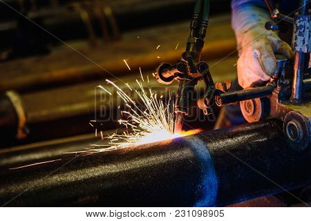 Worker Cutting Steel Pipe With Acetylene Welding Cutting Torch And Bright Sparks In Steel Constructi
