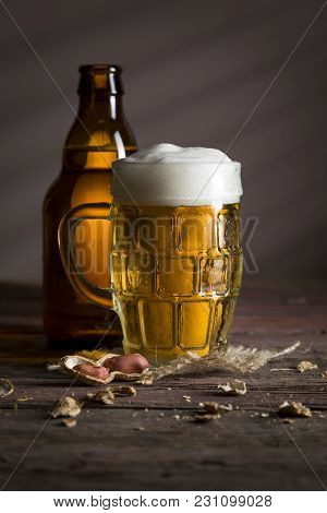 Beer Bottle And A Mug Of Cold Pale Beer Placed On A Burlap Coaster With Some Peanuts On A Rustic Woo