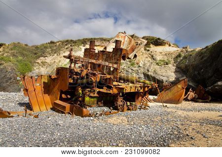 Half Buried In The Beach Sand, A Wrecked Pusher Boat