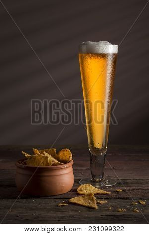 Glass Of Cold Pale Beer With A Bowl Of Tortilla Chips On A Rustic Wooden Table