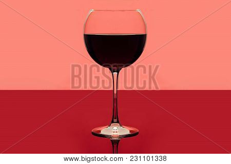 Red Wine. Drink Glass Of Red Wine On A Pink And Red Background. Alcoholic Beverage. Romantic Evening
