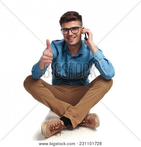 seated casual man talking on the phone makes the ok sign on white background