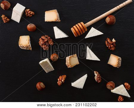 Cheese With Nuts On A Dark Stone Plate.