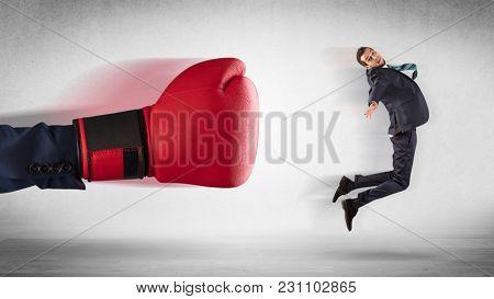 Big red boxing gloves hitting little businessman concept
