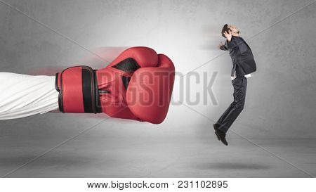 Businessman gets a hit from a giant hand with boxing gloves