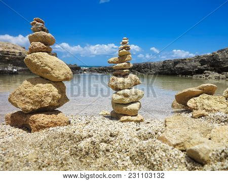 Piramide Stack Of Zen Stones Near Sea And Blue Sky Background
