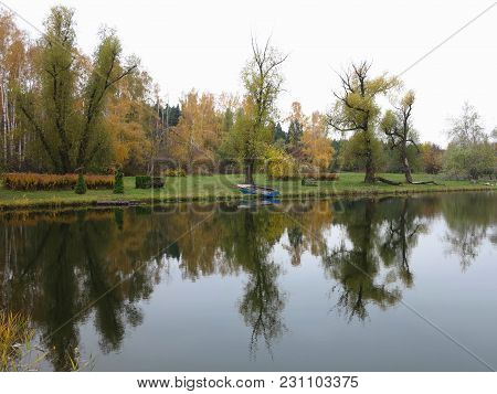 Autumn Landscape With Colorful Forest, Lake, Reflection And A Boat