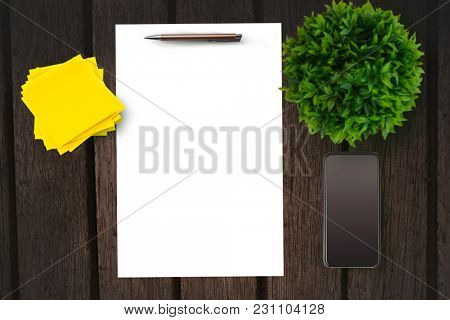Paper on table in front of plant and smartphone