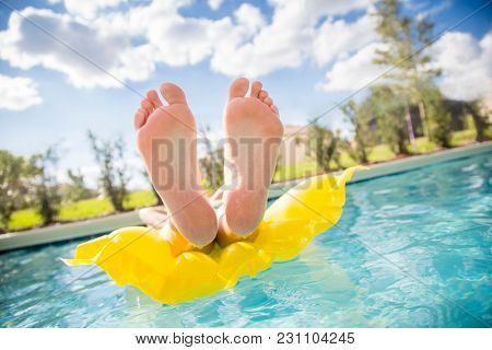 Beautiful sexy female feet relaxing while floating in a swimming pool.