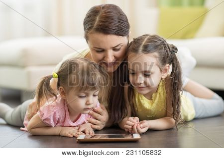 Mother With Children Daugters Lying On Floor And Looking At Tablet Pc