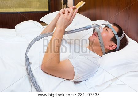 Middle Age Asian Man Laying In His Bed Wearing Cpap Mask And Using His Smart Phone At Night