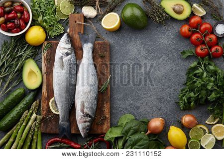 Fresh Raw Seabass And Ingredients For Cooking: Rosemary, Thyme, Lime, Lemon, Greens And Vegetables.