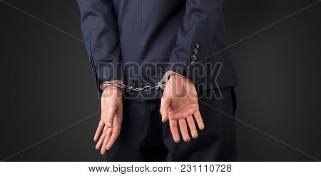 Close now arrested men hand with dark background and handcuffs