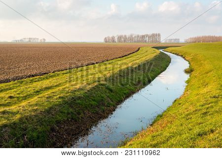 Water Surface Of A Meandering Ditch Reflects The White Clouds In The Blue Sky. The Field Next To The