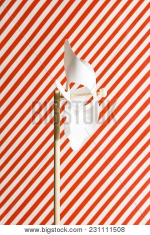 A White Pinwheel On A Striped Red And White Background
