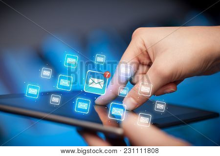 Female hands touching tablet with e-mail icons