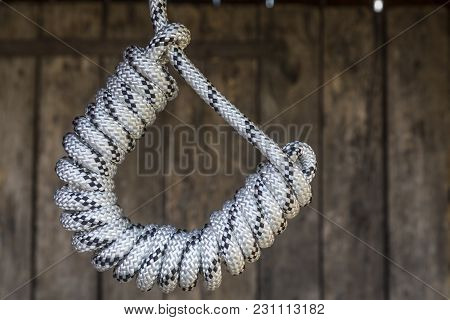Rope Knot On A Teak Wood Background.