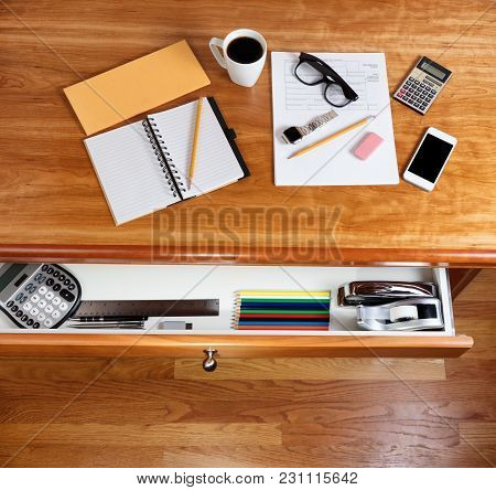 Overhead View Of Solid Cherry Desktop With Personal Income Forms And Office Supplies