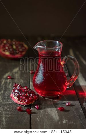 Cold Pomegranate Juice In A Transparent Glass Pitcher On Dark Wooden Background