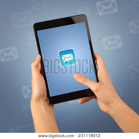 Female fingers touching tablet with mail icon on it