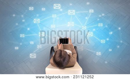 Mail symbols with woman using device in a beige chair