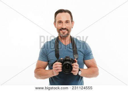 Portrait of a handsome mature man dressed in t-shirt holding photo camera isolated over white background