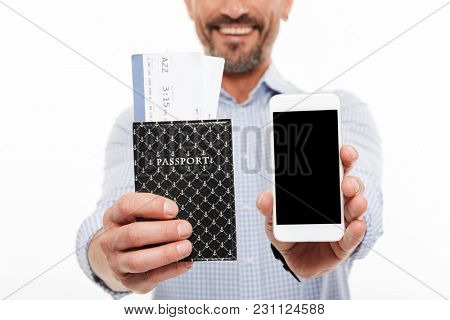 Close up of a happy mature man dressed in shirt holding passport with flying tickets and showing blank screen mobile phone isolated over white background