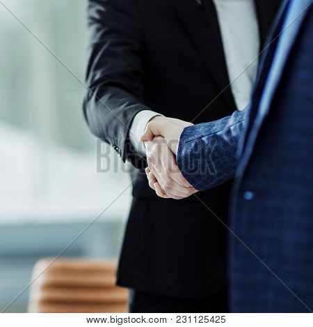Handshake Of Business Partners On The Background Of The Workplace.the Photo Has A Empty Space For Yo