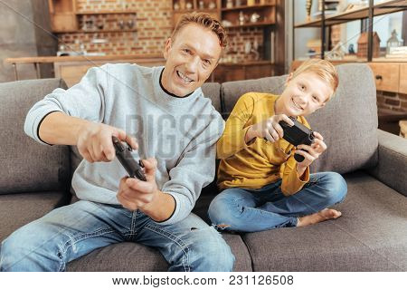 Favourite Entertainment. Happy Delighted Nice Father And Son Sitting On The Sofa And Holding Game Co