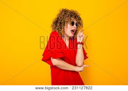 Portrait Of A White Scared Woman With Afrro Curly Hairstyle In Red Dress And Sunglasses Pointing At