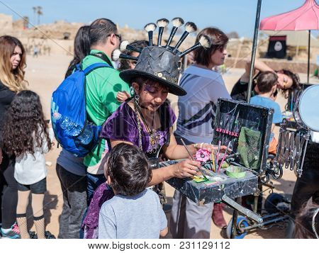 The Participant Of The Purim Festival Dressed In Fabulous Costume, Puts A Drawing On The Boy's Face