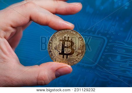 Golden Bitcoin Cryptocurrency in man`s hand. New Virtual money concept.