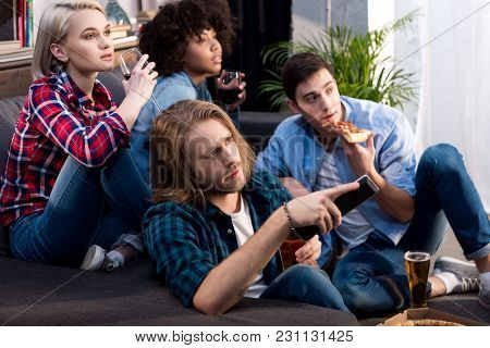 Multicultural Friends Watching Tv With Alcohol And Food At Home