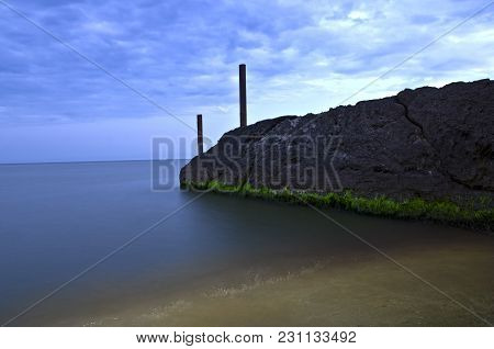 Concrete Breakwater In The Water On The Azov Sea Beach Shot In The Evening.