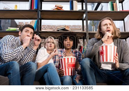 Shocked Multiethnic Friends Watching Horror Movie With Popcorn