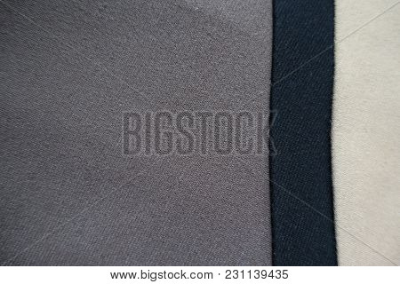 Narrow Black And Beige Ribbons Sewn To Grey Fabric